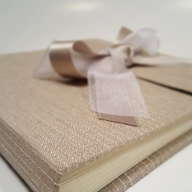 Photo album in beige striped fabric and decoration seams with ribbon in brown organza and satin