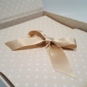 Photo album in beige fabric printed with polka dots and ivory satin ribbon.