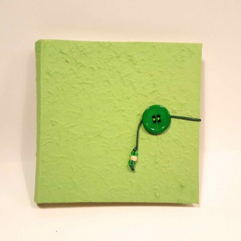 Photo album covered in green mulberry paper, waxed string and button closure on the cover.