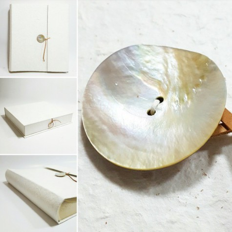 Photo album coated natural mulberry paper and, nacre button and closing with leather.