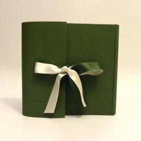 Album fotografico rivestito in tela cialux verde bosco, chiusura ad aletta e doppio fiocco in raso avorio e verde.