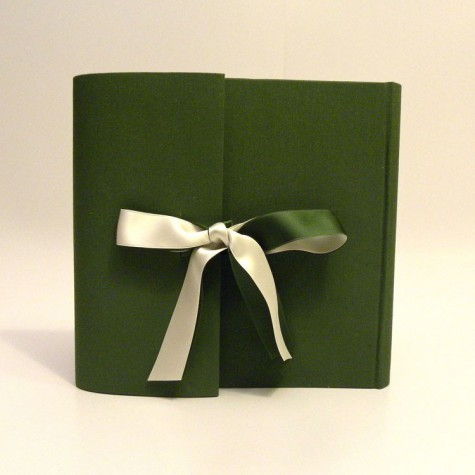 Photo album covered in green canvas, closing flap and double satin bow ivory and green.