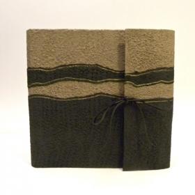 Album fotografico con aletta rivestito in carta Moonrock sabbia e nera, chiusura in cuoio nero a fiocco